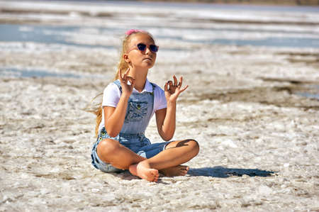 A little girl is engaged in yoga and meditation at a Spa resort. Concept of children's health recreation