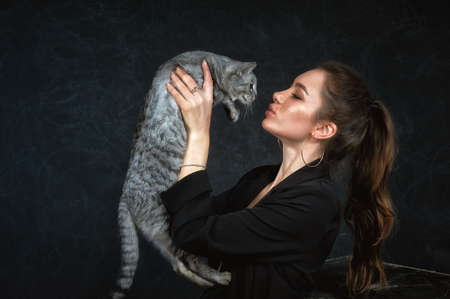 portrait of a young woman with a cat on a dark background. Man and animal look into each other's eyes