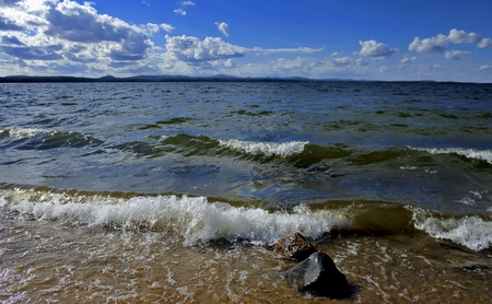 noisy wave is incident on the shore of the lake, fly spray around, large Cumulus clouds flying across the sky, South Ural, Uvildy Stock Photo