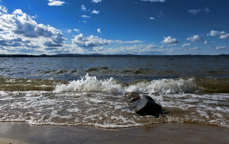 ural: noisy wave is incident on the shore of the lake, fly spray around, large Cumulus clouds flying across the sky, South Ural, Uvildy Stock Photo