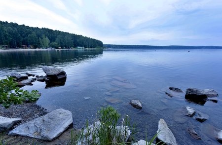 quiet lake Uvildy early in the morning, clear water, clear bottom, South Ural, in the distance are seen the Ural mountains