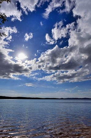 ural: bright blue sky with white clouds over the wooded shore of the lake, South Ural, Uvildy Stock Photo