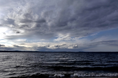 dark gray sky over the restless lake, the wind blows