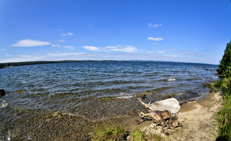 wooded and rocky shore on the background of the lake and the blue sky, fish-eye