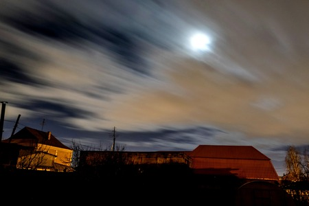view of the night moon sky with fast-flying clouds in the suburbs, wind, fog
