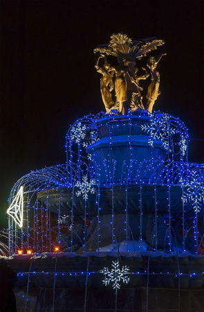 Christmas decoration of the fountain glows at night Editorial