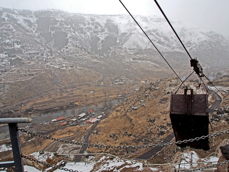 view of the Kura river valley from Vardzia monastery during spring snow and fog, right cable box for lifting loads from below