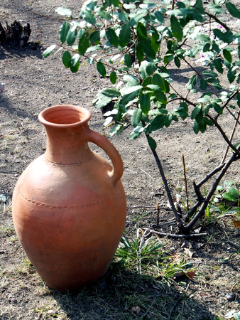 old clay jug on the ground in the yard of a roadside restaurant, performs decorative functions Foto de archivo