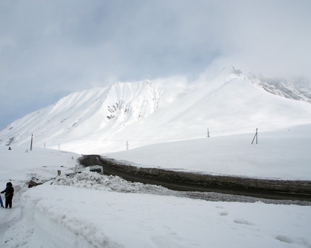 snowy landscape along the Georgian military road in spring during a snowstorm, snowdrifts on the sides as high as a car and above