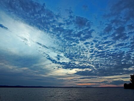 blue sunset sky over the lake with small clouds like a tortoise shell, southern Urals, blue hour