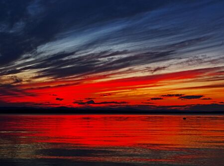 red sunset sky over the lake, dramatic lighting, fantastic cloud pattern, surreal landscape, southern Urals, lake Uvildy 免版税图像