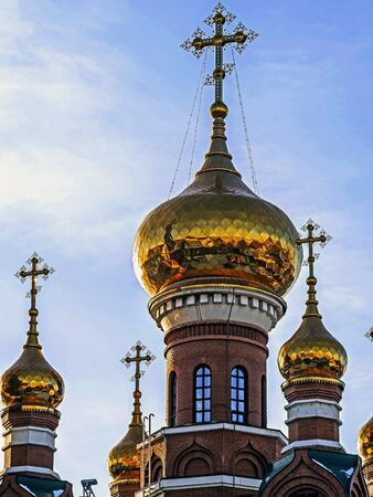 Golden domes of the Church of St. George the victorious in Chelyabinsk, view on the background of the winter evening sky Stock Photo