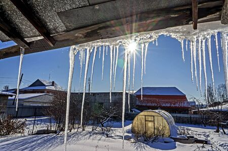 spring icicles hanging from the roof illuminated by the midday sun Stok Fotoğraf