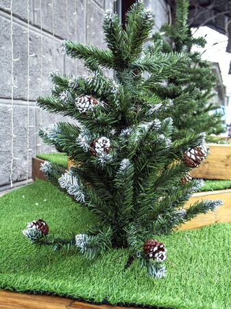 decorative green Christmas tree made of plastic near the store Standard-Bild