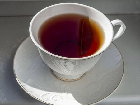 mug of fresh tea on the windowsill is illuminated by the sun Фото со стока - 146386488