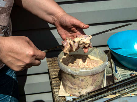 cook pierces meat pieces on a skewer for cooking kebabs, the cook's hands are visible