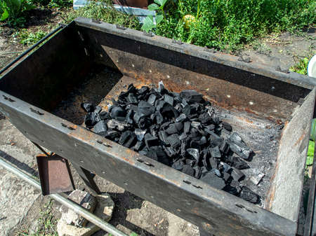 charcoal for cooking shish kebab is poured in a metal grill
