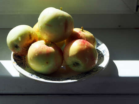 ripe fresh juicy apples in a plate on the windowsill