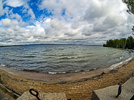 the lake shore in windy weather, the sky with Cumulus clouds, lake Uvildy, south Urals, lens fisheye