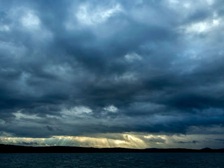 dark overcast sky over the lake on a summer evening, gloomy clouds, the opposite shore in the distance, lake Uvildy, southern Urals 免版税图像