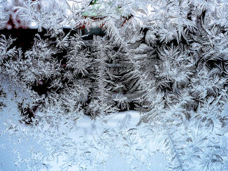 Frosty natural pattern on a winter window, texture of frosty patterns, dendritic image structure 免版税图像