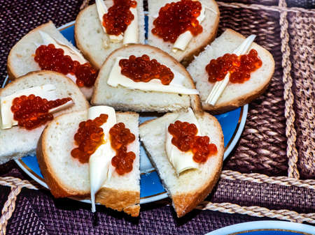 sandwiches with red caviar on white bread with butter are on a plate