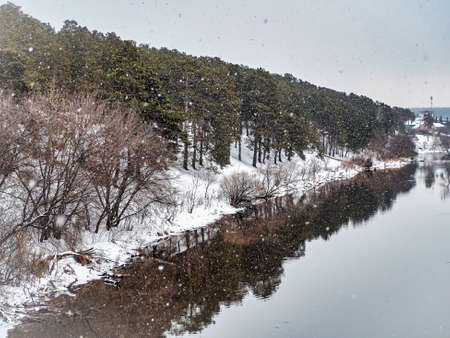 view from the bridge to the river in winter outside the city during a heavy snowfall, open water, snow-covered banks, forest, countryside, Southern Urals