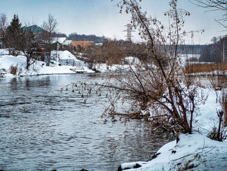 view from the bridge on the Miass River in winter outside the city during a heavy snowfall, open water, snow-covered banks, forest, countryside, Kashtak, Southern Urals 免版税图像