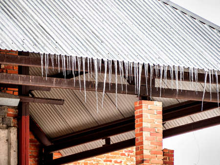 icicles on the roof of the house in early spring in cloudy weather