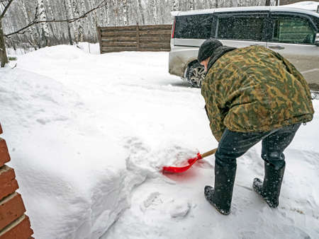 man removes fresh snow with a shovel during a snowfall