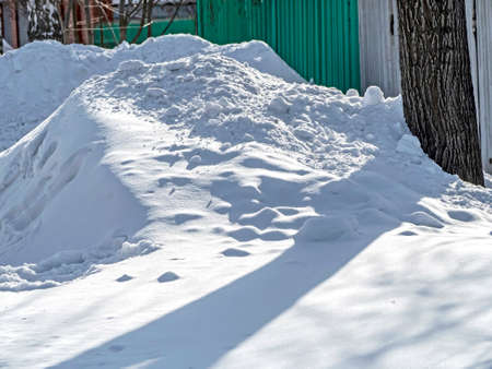 snowdrift and clumps of snow near the fence 免版税图像