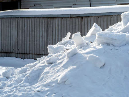 snowdrift and clumps of snow near the fence illuminated by the spring sun