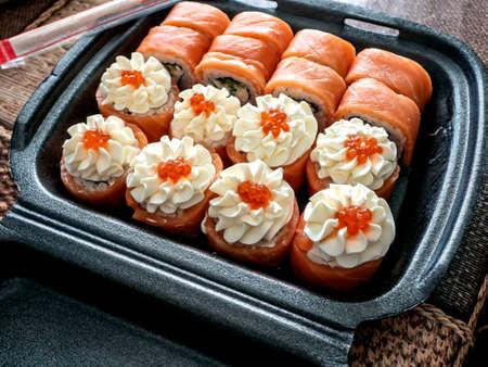 bright little set of sushi rolls in a plastic box Foto de archivo