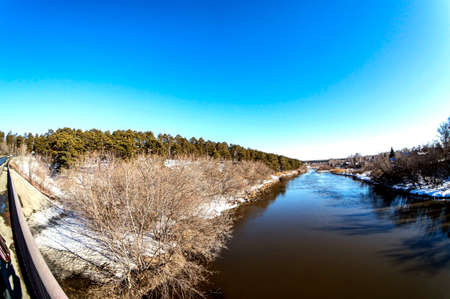 view from the bridge to the river in the spring outside the city, open water, snow melts on the banks, forest, countryside, Miass River, Southern Urals
