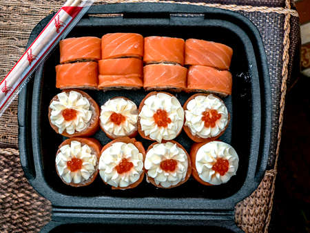 bright delicious little set of sushi rolls in a plastic box 免版税图像