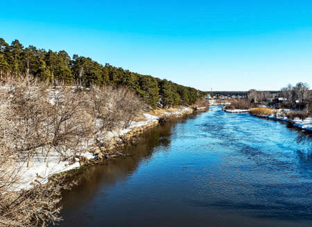 view from the bridge to the river in the spring outside the city in the evening, the sun shines, snow melts, pine forest, countryside, Miass River near the village of Kashtak, Southern Urals 免版税图像
