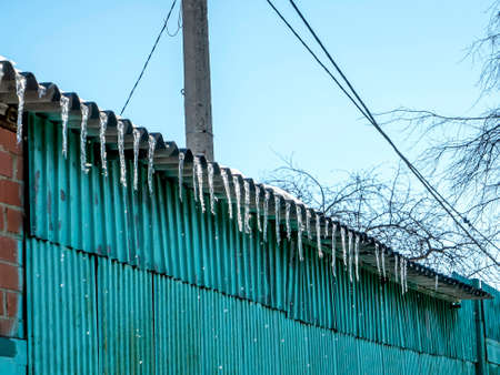 Icicles hang from the edge of the roof of the house and melt on a warm day 免版税图像