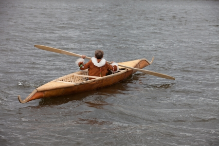 stagnate: traditional boat of Siberia with the fisherman in national dress