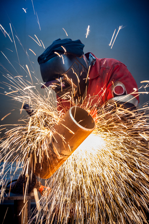 Welder working in the red uniform and a mask, he welds pipe bright sparks fly 免版税图像