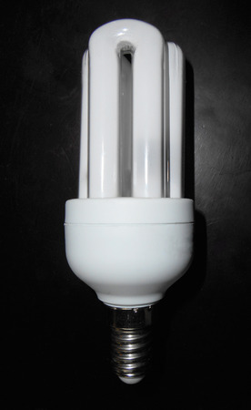 Compact fluorescent light-bulb on wooden table photo