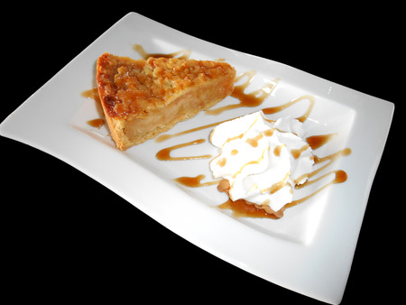 Apple pie with whipped cream isolated on black photo