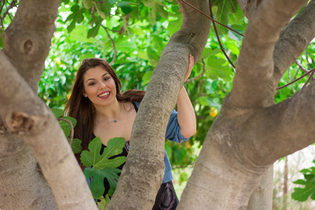 fig tree: Young beautiful caucasian girl smiling behind a fig tree. Stock Photo