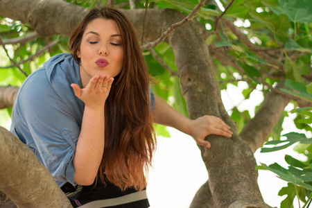 fig tree: Young beautiful caucasian girl sending a kiss while being on a big fig tree. Stock Photo