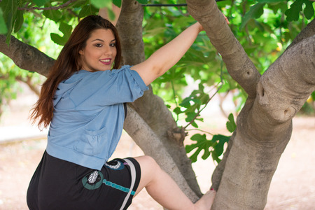 Young beautiful caucasian girl climbing on a fig tree. Stock Photo