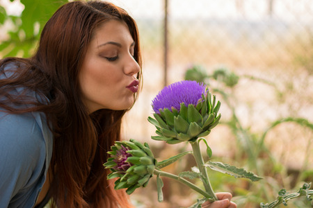 caucasian girl: Young beautiful caucasian girl kissing an artichoke flower Stock Photo