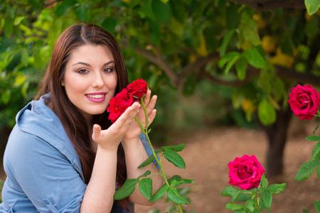 roses rouges: Belle jeune fille caucasien tenant des roses rouges dans le jardin en souriant.
