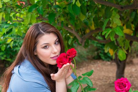 rosas rojas: La muchacha hermosa joven cauc�sica que sostiene rosas rojas en el jard�n sonriendo. Foto de archivo