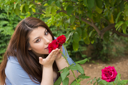 smelling: Young beautiful Caucasian girl smelling the roses in the garden.
