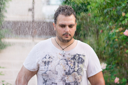 rain wet: Man standing with his eyes closed in the rain. Stock Photo