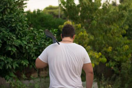 hombre fuerte: Joven agricultor se va con una pala en la espalda. Foto de archivo